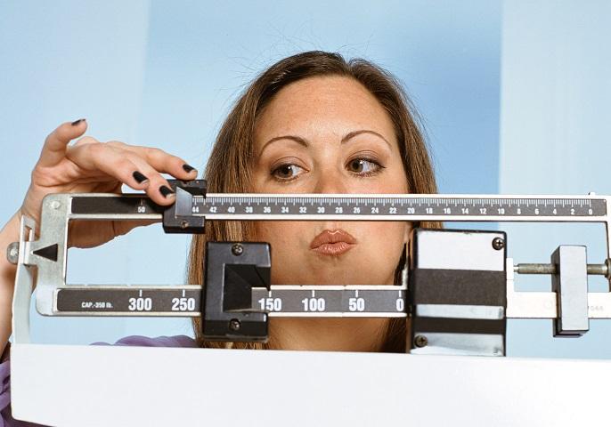 Frau pr�ft ihr Gewicht auf einer Waage