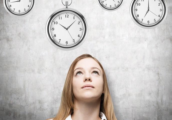 Frau mit Uhren, die verschiedene Uhrzeiten anzeigen.